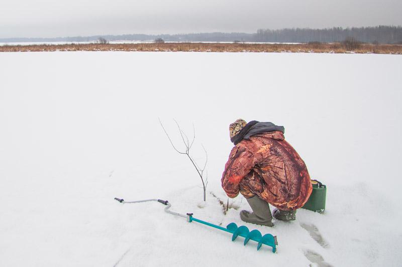 Рыболов ловит рыбу на льду